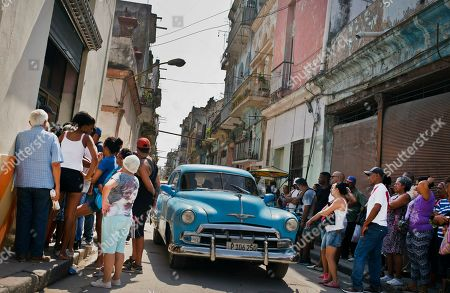 People wait in line to buy chicken at a government-run grocery store in Havana, Cuba, . The Cuban government said Friday, that it will begin widespread rationing of chicken, eggs, rice, beans, soap and other basic products in the face of a grave economic crisis