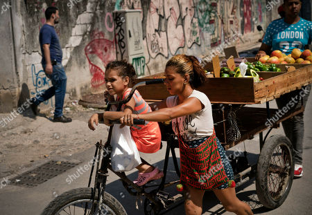 A girl perches on a bike pulling a vegetable cart in Old Havana, Cuba, . The Cuban government said Friday, that it will begin widespread rationing of chicken, eggs, rice, beans, soap and other basic products in the face of a grave economic crisis