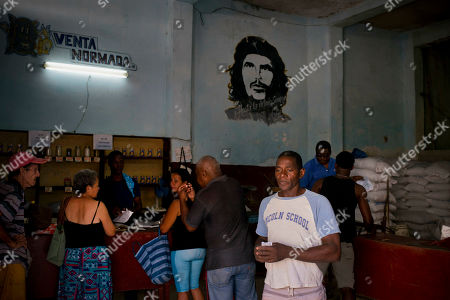People shop for food in a government-run store in Havana, Cuba, . The Cuban government said Friday, that it will begin widespread rationing of chicken, eggs, rice, beans, soap and other basic products in the face of a grave economic crisis