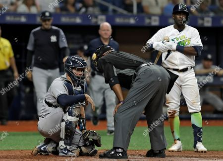 Gary Sanchez, Laz Diaz, Guillermo Heredia. Home plate umpire Laz Diaz, center, talks to New York Yankees catcher Gary Sanchez, left, after he was hit on the head on a swing by Tampa Bay Rays' Guillermo Heredia, right, during the eighth inning of a baseball game, in St. Petersburg, Fla. Sanchez stayed in the game