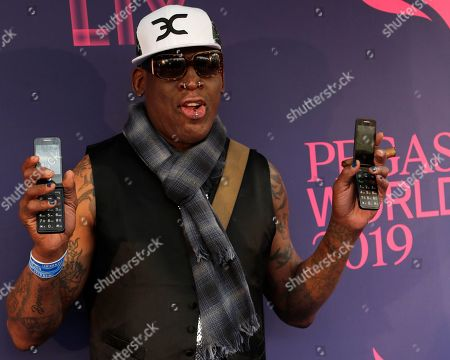 Stock Picture of Dennis Rodman poses with two flip phones on the blue carpet at the Pegasus World Cup Invitational Horse Race at Gulfstream Park in Hallandale Beach, Fla. The owner of a Southern California yoga studio is accusing Dennis Rodman of helping three people steal more than $3,500 in merchandise from his business. Ali Shah says security cameras captured the former NBA star walking into Vibes Hot Yoga in Newport Beach, with his alleged accomplices