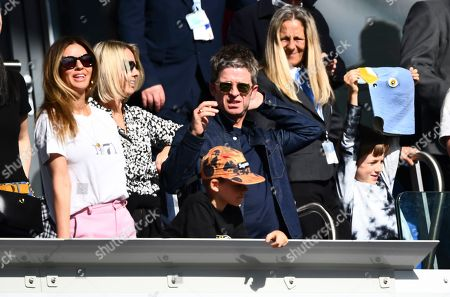 Noel Gallagher, his eldest son Donovan and his wife Sara Macdonald look on as younger son Sonny holds up a pigeon mask