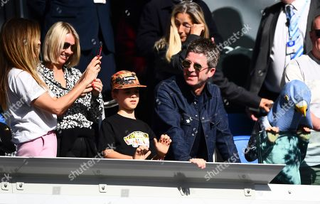Noel Gallagher and his son Donovan looks on as his wife Sara Macdonald takes a photo of younger son Sonny wearing a pigeon mask