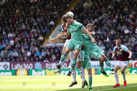 Burnley defender Ben Mee (6) heads the ball in front of Arsenal defender Laurent Koscielny (6) and Arsenal defender Nacho Monreal (18) during the Premier League match between Burnley and Arsenal at Turf Moor, Burnley