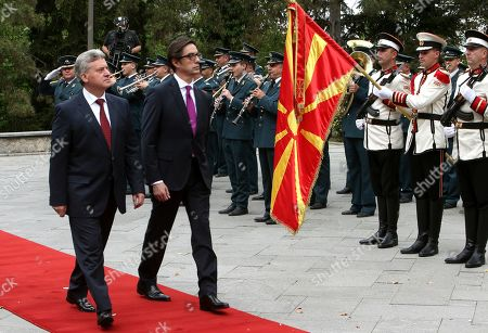 Stock Image of Stevo Pendarovski, second from left, the new elected President of North Macedonia and the former President Gjorge Ivanov, left, inspect an honor guard squad during a ceremony to hand over duties, at the presidential palace in Skopje, North Macedonia, . Pendarovski has been sworn in as the new president of North Macedonia, promising he will serve all citizens in a deeply divided society and will lobby European Union leaders to approve the start of his country's accession talks in June