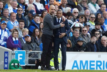 Manchester City coach Pep Guardiola and Brighton manager Chris Hughton, right, embrace each other during the English Premier League soccer match between Brighton and Manchester City at the AMEX Stadium in Brighton, England