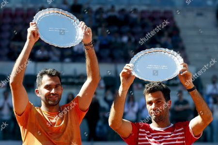 Horia Tecau of Romania (L) and Jean-Julien Rojer of Netherlands (R) pose with their trophies after winning the men's doubles final at the Mutua Madrid Open tennis tournament in Madrid, Spain, 12 May 2019.