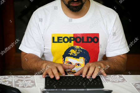 Wearing a T-shirt featuring Leopoldo Lopez, Venezuelan opposition leader Freddy Guevara, exiled at the Chilean ambassador's residence, types on a computer keyboard in Caracas, Venezuela. Guevara, in his first televised interview since taking refuge in the lush diplomatic compound 18 months ago, said as foreign embassies in Caracas fill up with dissidents the world will be forced to take notice of how Nicolas Maduro's clinging to power is not only inflicting more damage on what's left of the rule of law in Venezuela but spilling over its borders as well