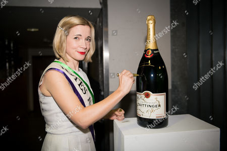 Lucy Worsley signs a champagne bottle