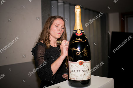 Jessica Hynes signs a champagne bottle