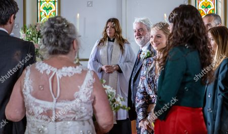 Ep 8485 Thursday 23rd May 2019 - 1st Ep The day of the wedding soon arrives and Lisa Dingle, as played by Jane Cox, comes downstairs in her wedding dress. Lydia, Lisa and Belle's excitement peaks, but as they leave they find the pigs have escaped and are running loose. The bridal party chase the escaped pigs outside Homestead. Cain falls flat in the mud. Determined Lisa prepares to sort it out herself. Meanwhile at the Church a nervous Zak Dingle, as played by Steve Halliwell, and the wedding guests all sit patiently, waiting for Lisa to arrive. The congregation are in shock as a filthy Lisa arrives fresh from tackling the pigs. Everybody bursts into laughter as Lisa makes her way up the aisle towards her groom. With Harriet Finch, as played by Katherine Dow Blyton.
