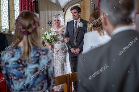 Ep 8485 Thursday 23rd May 2019 - 1st Ep The day of the wedding soon arrives and Lisa Dingle, as played by Jane Cox, comes downstairs in her wedding dress. Lydia, Lisa and Belle's excitement peaks, but as they leave they find the pigs have escaped and are running loose. The bridal party chase the escaped pigs outside Homestead. Cain falls flat in the mud. Determined Lisa prepares to sort it out herself. Meanwhile at the Church a nervous Zak Dingle, as played by Steve Halliwell, and the wedding guests all sit patiently, waiting for Lisa to arrive. The congregation are in shock as a filthy Lisa arrives fresh from tackling the pigs. Everybody bursts into laughter as Lisa makes her way up the aisle towards her groom. With Cain Dingle, as played by Jeff Hordley.