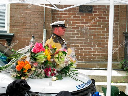 A Savannah police officer stands at attention next to a patrol SUV where law enforcement officers and local officials laid bouquets of flowers, as a memorial to a slain patrol sergeant outside the police headquarters in Savannah, Georgia. Authorities say Sgt. Kelvin Ansari died after he was shot Saturday, May 11, 2019, while responding to an armed robbery outside a Savannah barber shot. A second officer survived after being shot in the leg. The suspect, Edward Fuller III, was shot and killed by police