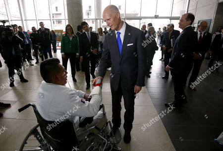 US Senator Rick Scott (C) greets a disabled serviceman during a visit to the Center for Inclusive Rehabilitation (CRI), where sport and employment inclusion are extended to members of the Colombian armed forces wounded in combat, in Bogota Colombia, 13 May 2019. At least eight people have been killed in Colombia furing 2019 by anti-personnel mines, including six soldiers and one police officer according to Colombian Defense Minister Guillermo Botero.