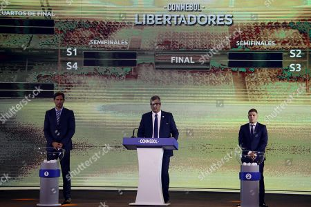 Stock Photo of The director of competitions of The South American Football Confederation Federico Nantes (C) along with soccer players Roque Santa Cruz (L) of Paraguay and Juan Fernando Quintero (R) of Colombia participate attend the draw of the Copa Libertadores and the Copa Sudamericana soccer tournaments at the Conmebol headquarter in Luque, Paraguay, 13 May 2019.