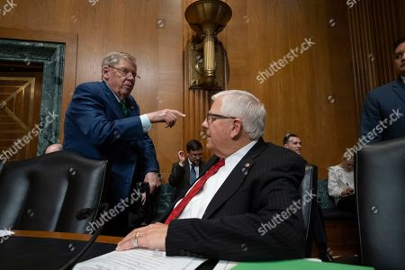 "Johnny Isakson, Mike Enzi. Sen. Johnny Isakson, R-Ga., top left, greets, Sen. Mike Enzi, R-Wyo., chairman of the Senate Budget Committee, as the Senate Finance Committee prepares for a hearing called ""Challenges in the Retirement System,"" on Capitol Hill in Washington"