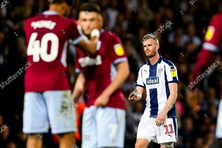 Chris Brunt of West Bromwich Albion looks distraught as he passes his captains armband to James Morrison after he is sent off after a 2nd yellow card
