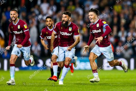 Jack Grealish of Aston Villa runs with Mile Jedinak and Conor Hourihane as the players celebrate after Aston Villa win the game on penalties to reach the Sky Bet Championship Final at Wembley
