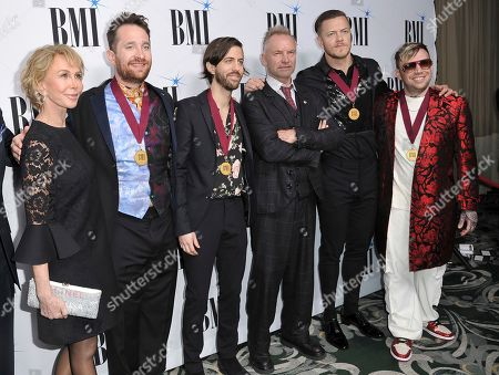 Trudie Styler, Sting, Daniel Platzman, Wayne Sermon, Dan Reynolds, Ben McKee. Trudie Styler, left, honoree Sting, third right, and members of Imagine Dragons, winners of the President's Award, Daniel Platzman, from second left, Wayne Sermon, Dan Reynolds and Ben McKee, arrive at the 67th annual BMI Pop Awards, at the Beverly Wilshire Hotel in Beverly Hills, Calif