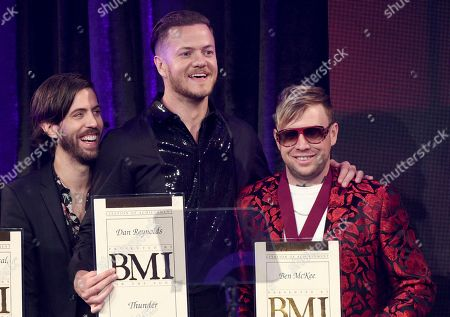 "Wayne Sermon, Dan Reynolds, Ben McKee. Wayne Sermon, from left, Dan Reynolds and Ben McKee, of Imagine Dragons, accept an award for their song ""Thunder"" at the 67th annual BMI Pop Awards, at the Beverly Wilshire Hotel in Beverly Hills, Calif"