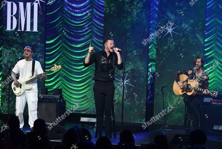 Ben McKee, Dan Reynolds, Wayne Sermon. Ben McKee, from left, Dan Reynolds and Wayne Sermon, of Imagine Dragons, winners of the President's award, perform at the 67th annual BMI Pop Awards, at the Beverly Wilshire Hotel in Beverly Hills, Calif