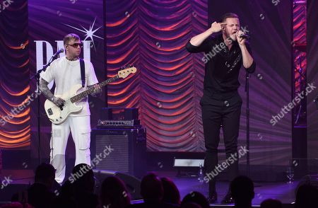 Ben McKee, Dan Reynolds. Ben McKee, left, and Dan Reynolds, of Imagine Dragons, winners of the President's award, perform at the 67th annual BMI Pop Awards, at the Beverly Wilshire Hotel in Beverly Hills, Calif