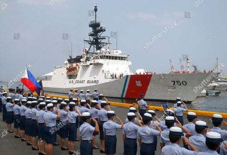 Philippine Coast Guard personnel salute to welcome the U.S. Coast Guard National Security Cutter Bertholf (WMSL 750) as it arrives for a port call in the first visit by a U.S. cutter in over seven years, in Manila, Philippines. Capt. John Driscoll, commanding officer of the Bertholf, told reporters that two Chinese Coast Guard ships were spotted off the South China Sea while they were conducting a joint exercise with Philippine Coast Guard