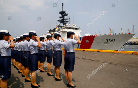 Stock Photo of Philippine Coast Guard personnel salute to welcome the U.S. Coast Guard National Security Cutter Bertholf (WMSL 750) as it arrives for a port call in the first visit by a U.S. cutter in over seven years, in Manila, Philippines. Capt. John Driscoll, commanding officer of the Bertholf, told reporters that two Chinese Coast Guard ships were spotted off the South China Sea while they were conducting a joint exercise with Philippine Coast Guard