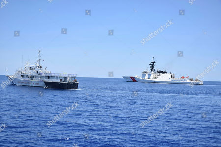 In this May 14, 2019, photo, photo provided by the Philippine Coast Guard, U.S. Coast Guard Cutter Bertholf, right, and Philippine counterpart BRP Batangas conduct joint search and rescue and capability-building exercises off the South China Sea west of the Philippines. Captain John Driscoll, commanding officer of the U.S. Coast Guard National Security Cutter Bertholf (WMSL 750), told reporters, two Chinese Coast Guard ships were spotted off the South China Sea while they were conducting the joint exercise with Philippine Coast Guard
