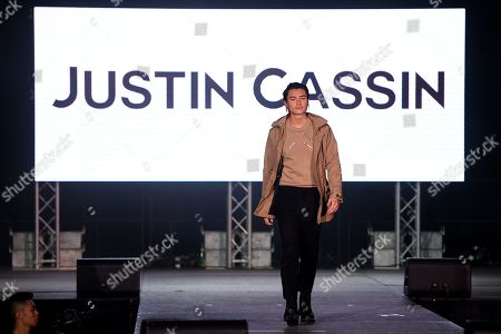 Australian actor Tim Kano presents a creation by Justin Cassin during the Mercedes-Benz Fashion Week Australia at Luna Park in Sydney, 15 May 2019. The fashion event runs from 12 to 17 May.