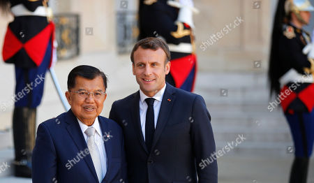 French President Emmanuel Macron, right, greets Indonesia's Vice-President Jusuf Kalla during arrivals at the Elysee Palace, in Paris, . Several world leaders and tech bosses are meeting in Paris to find ways to stop acts of violent extremism from being shown online