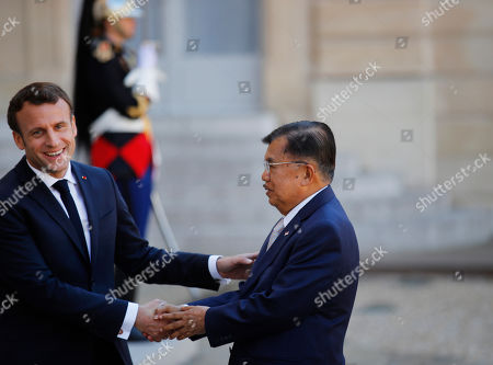 French President Emmanuel Macron, left, greets Indonesia's Vice-President Jusuf Kalla during arrivals at the Elysee Palace, in Paris, . Several world leaders and tech bosses are meeting in Paris to find ways to stop acts of violent extremism from being shown online