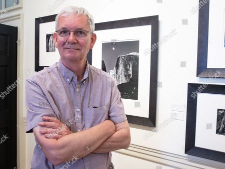 Photographer, Martin Parr, at the Exhibition standing in front of an Ansell Adams print. Press day at Photo London Exhibition which runs at Somerset House, London from 16-19 May. Photo London is a major exhibition featuring work from leading photographers spanning the last 150 Years.
