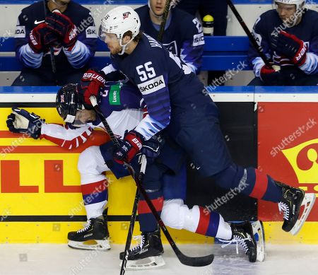 Noah Hanifin of the US, right, checks Great Britain's Luke Ferrara, left, during the Ice Hockey World Championships group A match between the United States and Great Britain at the Steel Arena in Kosice, Slovakia