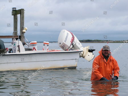 This photo shows Ken Knutsen harvesting oysters from a plot of Barnegat Bay in Barnegat Light, N.J. Matt Gregg, who owns an aquaculture business growing shellfish in the bay, says New Jersey environmental authorities gave him a permit in December for a pick-your-own shellfish plot, then told him such activity would not be allowed just two weeks before the pick your own venture was to launch