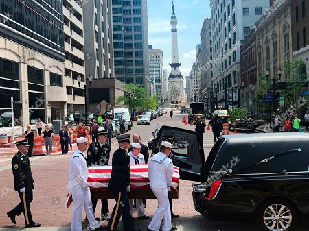 A military honor guard loads the casket of former Sen. Richard Lugar into a hearse outside the Indiana Statehouse, in Indianapolis for the procession to his funeral. The procession is taking the casket through the streets of Indianapolis on the way to his funeral. The procession paused at the Indianapolis City-County Building beneath a large garrison flag in recognition of his time as the city's mayor before his first election to the Senate in 1976