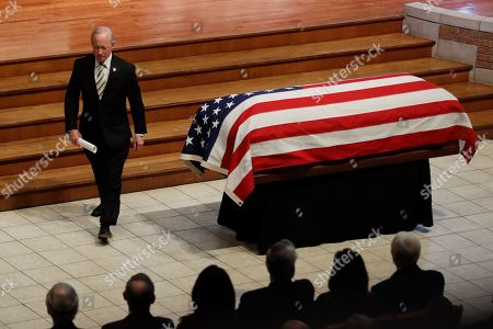 """Former Indiana Governor Mitch Daniels, president of Purdue University, walks past the casket of Sen. Richard Lugar after speaking during a funeral service, in Indianapolis. Lugar was a longtime Republican senator and former Indianapolis mayor who's been hailed as an """"American statesman"""" since he died April 28 at age 87"""