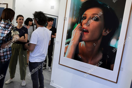 Stock Picture of People chat next to an artwork by German artist Julian Rosefeldt during the opening of the ARCO art fair in Lisbon . Fifty two art galleries are represented at the fair that runs until Sunday