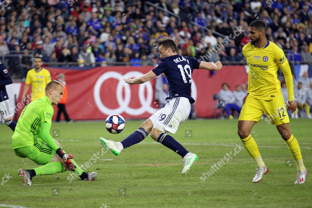 New England Revolution's Antonio Mlinar Delamea, center, clears the ball away as goalkeeper Cody Cropper, left, defends and Chelsea's Ruben Loftus-Cheek (12) pressures on the play during the second half of a friendly soccer match, in Foxborough, Mass