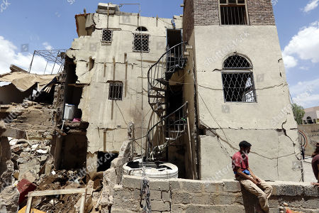 Stock Picture of A Yemeni sits amongst the debris of destroyed building damaged after an airstrike at a neighborhood in Sana?a, Yemen, 16 May 2019.  According to media reports, the Saudi-led military coalition intensified its airstrikes on the Yemeni capital Sana?a by targeting several positions and killing at least six Yemenis and wounding at least 52 others, in retaliation after the Iranian-aligned movement in Yemen allegedly attacked Saudi and Emirates oil ships.