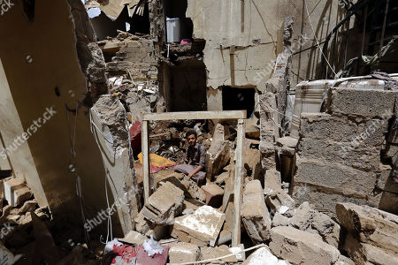 A Yemeni sits amongst the debris of destroyed building damaged after an airstrike at a neighborhood in Sana?a, Yemen, 16 May 2019.  According to media reports, the Saudi-led military coalition intensified its airstrikes on the Yemeni capital Sana?a by targeting several positions and killing at least six Yemenis and wounding at least 52 others, in retaliation after the Iranian-aligned movement in Yemen allegedly attacked Saudi and Emirates oil ships.