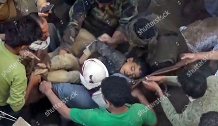 In this frame grab from from video, people carry a child's body after pulling it out from rubble following Saudi-led coalition airstrikes that killed at least six, including four children, officials said, in the residential center of the capital, Sanaa, Yemen. The Sanaa airstrikes came after Yemen's Iran-backed Houthi rebels, who control the capital, launched a drone attack earlier in the week on a critical oil pipeline in Saudi Arabia, Tehran's biggest rival in the region