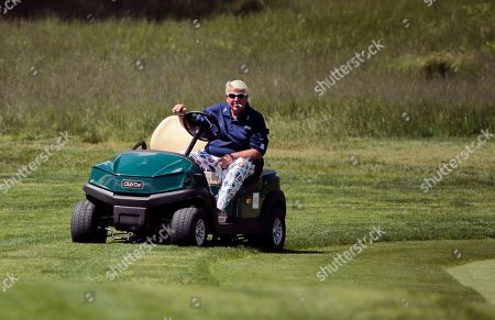 John Daly drives a golf cart along the 16th fairway during the first round of the PGA Championship golf tournament, at Bethpage Black in Farmingdale, N.Y
