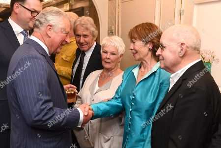 Prince Charles shaking hands with Celia Imrie as Judi Dench watches on