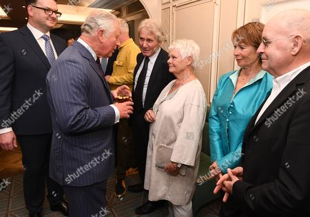 Prince Charles speaks with Judi Dench as Celia Imrie watches on