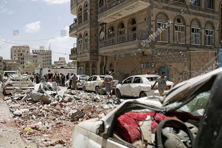People inspect the site of an airstrike by Saudi-led coalition in Sanaa, Yemen, Thursday, May, 16, 2019. Yemen's human rights minister says heavy fighting is underway in the country's south as rebel Houthis push to gain more territory from government forces and their allies. The clashes come as the Saudi-led coalition carried out airstrikes on the capital, Sanaa, earlier on Thursday, targeting the Houthis and killing at least three civilians