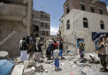 Stock Photo of People inspect the site of an airstrike by Saudi-led coalition in Sanaa, Yemen, Thursday, May, 16, 2019. Yemen's human rights minister says heavy fighting is underway in the country's south as rebel Houthis push to gain more territory from government forces and their allies. The clashes come as the Saudi-led coalition carried out airstrikes on the capital, Sanaa, earlier on Thursday, targeting the Houthis and killing at least three civilians