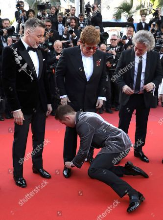 Taron Egerton, Elton John, David Furnish, Dexter Fletcher. Actor Taron Egerton, center, ties the shoelaces of singer Elton John, center top, as they pose with producer David Furnish, director Dexter Fletcher, actor Richard Madden, producer Adam Bohling and music producer Giles Martin upon arrival at the premiere of the film 'Rocketman' at the 72nd international film festival, Cannes, southern France