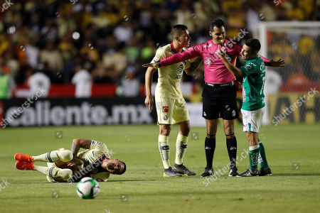 America's Andres Uribe, center, and Leon's Jean Meneses, right, protest to referee Jorge Perez Duran, second from right, as America's Nicolas Castillo grimaces in pain on the ground during the Mexico soccer league semi-final first leg match against Leon at La Corregidora stadium in Queretaro, Mexico, . Leon won the match 1-0