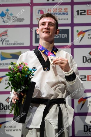 Bradly Sinden of Great Britain receives the winners medal after winning the Mens 68kg Final fight against Javier Perez Polo of Spain.